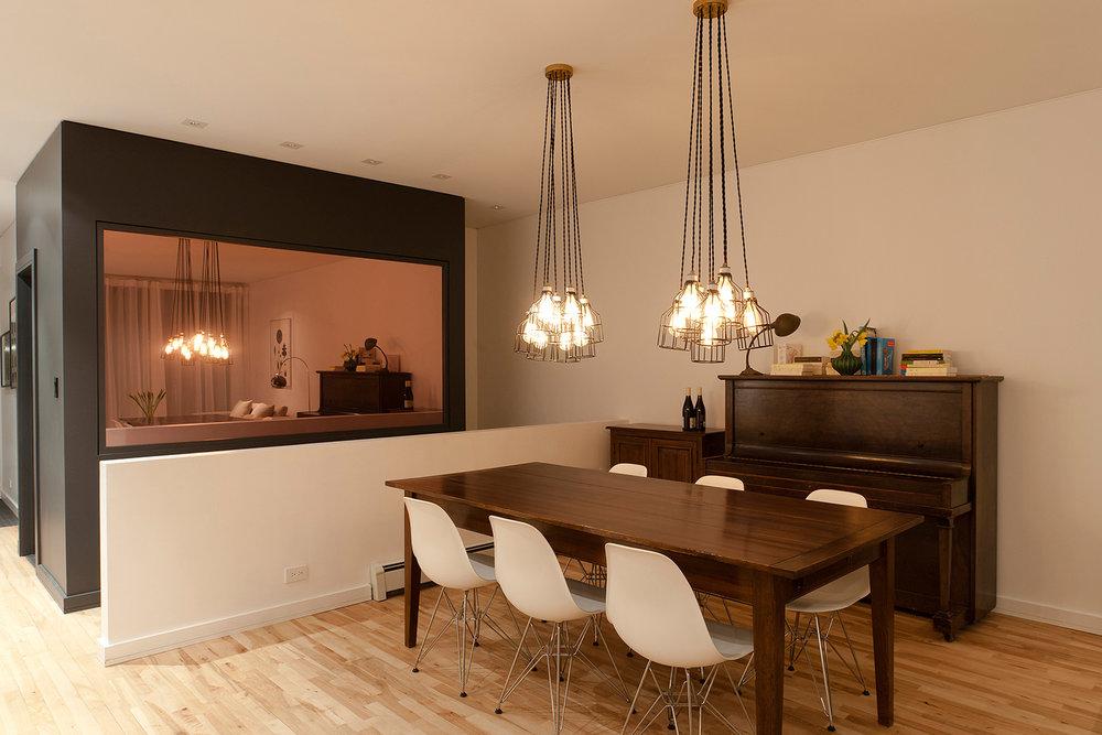 Rénovation de cuisine. Îlot avec comptoir de quartz blanc et intégration d'une desserte en bois existante. Dos de l'îlot fini en acier peint bleu. Dosseret custom avec panneaux de métal perforé bleu