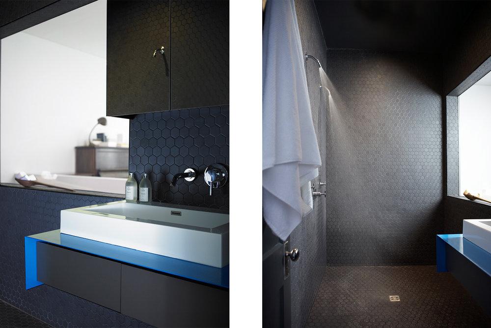 Rénovation de salle de bain monochrome dans un appartement. Douche double ouverte avec drain central. Mosaïque hexagonale noir. Meuble lavabo suspendu avec comptoir de stainless fini bleu (peinture cuite)