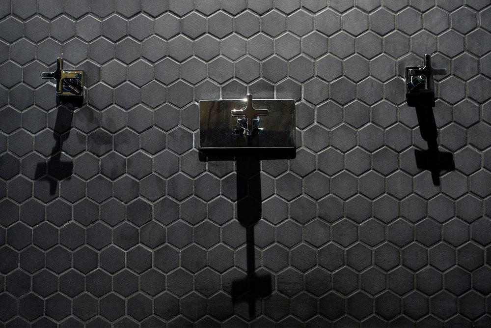 Rénovation de salle de bain monochrome dans un appartement. Vue détaillée de la robinetterie de la douche sur mur de mosaïque hexagonale noir.