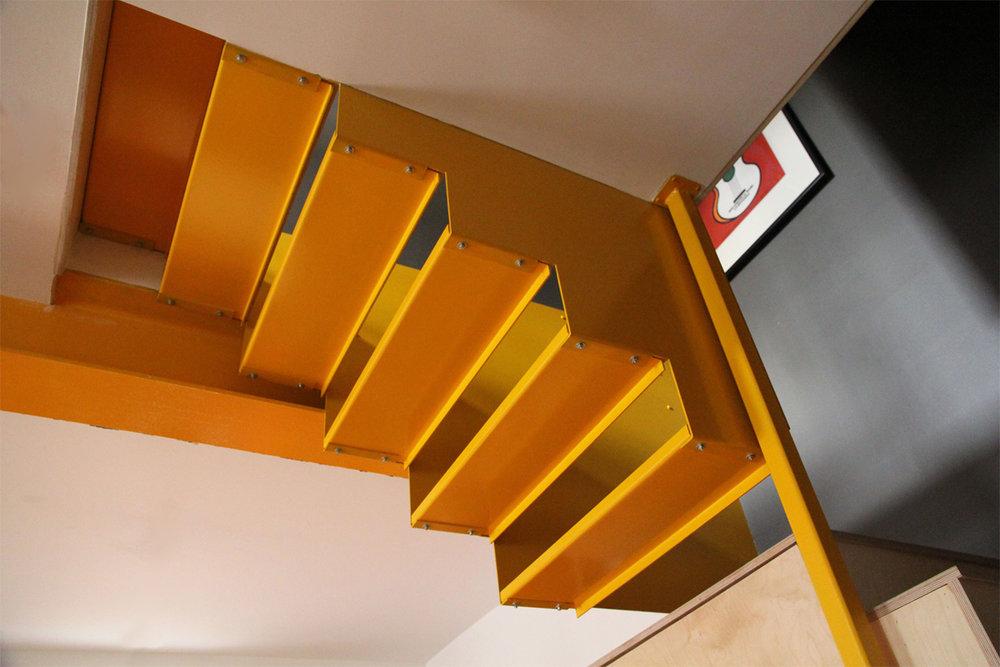 Nouvel escalier en acier peint jaune suspendu à l'étage. Contremarche ouverte