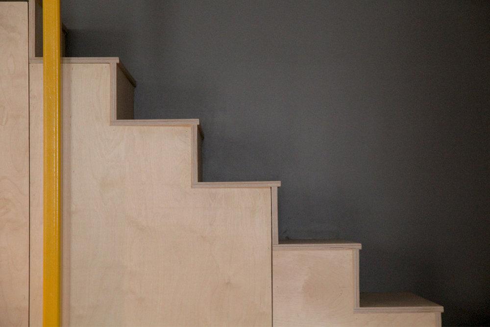 Escalier fait de contreplaqué. Structure tenant l'étage en tubulaire d'acier carré 4x4 jaune.