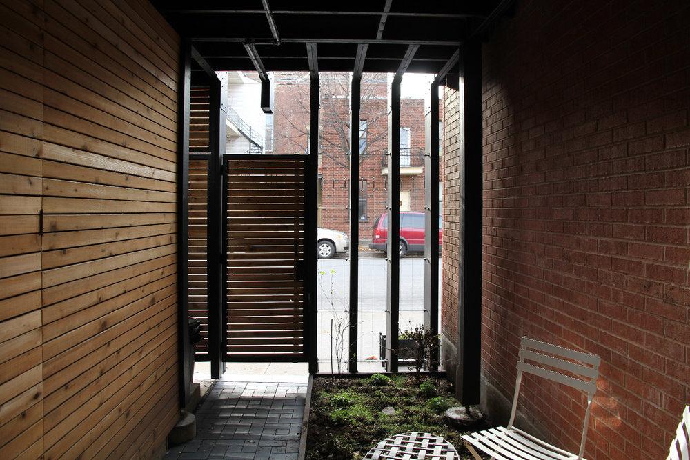 Petite cour intérieur sous la terrasse en bois. Parois de bois et mur de briques rouge