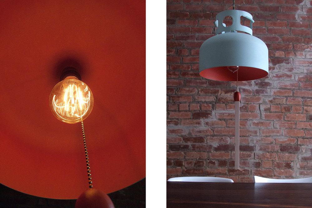 Lampe faite à partir d'une bombonne de propane. Une allumette en format géant est suspendue au centre. Extérieur peint bleu gris et intérieur fini rouge ocre.