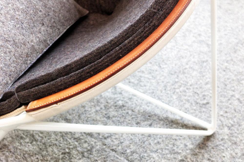 Détail d'une chaise faite sur mesure pour l'hôtel La ferme. Recouvrement en feutre avec toile blanche et renfort en cuire brun. Structure métallique en tige blanche