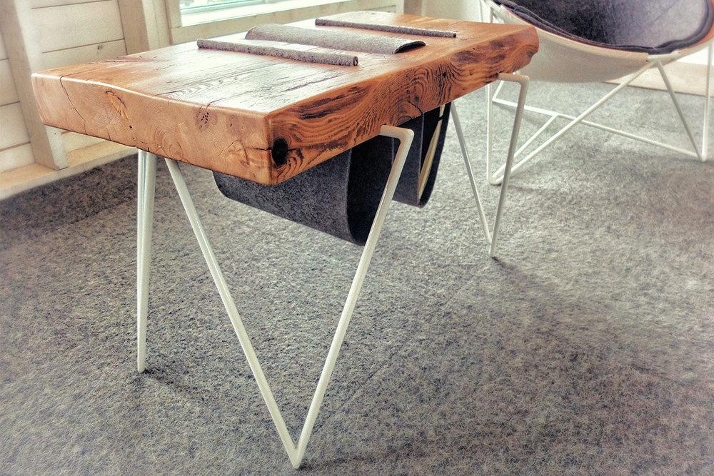Table basse faite sur mesure avec plateau de bois massif et piètement en tige métallique blanche. Insertion de feutre pour support de magazines.