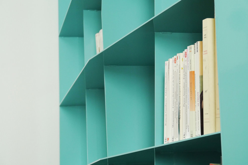 Bibliothèque faite sur mesure pour un condo moderne. Structure en plaque d'acier fini peinture cuite turquoise.