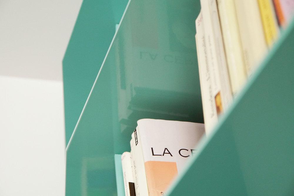 Vue rapprochée d'une étagère de la bibliothèque faite sur mesure, fini en peinture cuite turquoise.