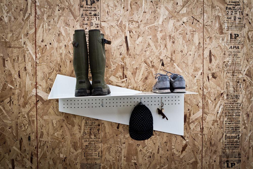 Vue de face de la tablette d'acier fini peinture cuite blanche. Plaque verticale perforée pour suspendre des accessoires. Support à chaussures mural