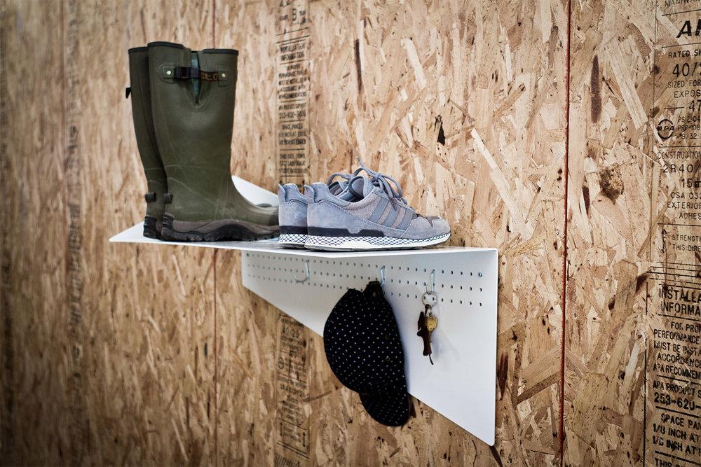 Support à chaussures mural fini peinture cuite blanche. Plaque verticale perforée pour suspendre des accessoires.