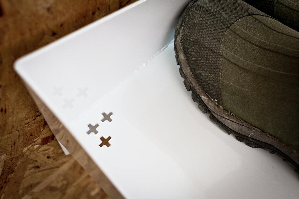 Tablette d'acier fini powder coat blanche. Support à chaussures mural. Détail du motif perforé pour l'écoulement de l'eau