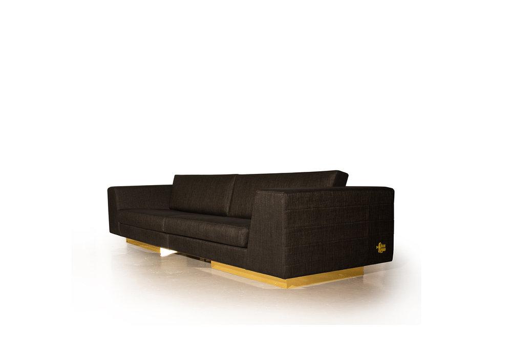 Vue de biais du sofa 5 places réalisé sur mesure. Finition en tissu italien avec fil d'or.
