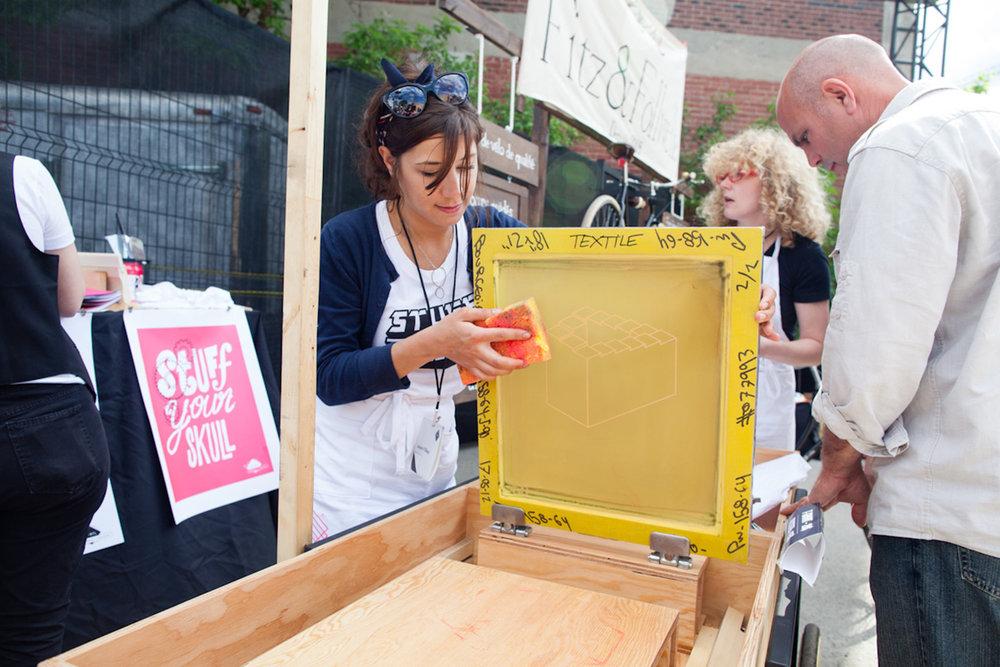 Sérigraphie sur t-shirt pour un événement en extérieur. Station de sérigraphie mobile. Structure et cadre d'acier fini en contreplaqué.