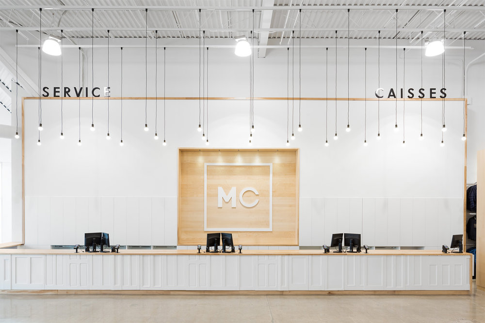 Comptoir caisse d'une boutique de vêtement. Utilisation de portes récupérées et façades d'armoires. Comptoir de merisier massif. Rangement dissimulé. Logo blanc dans niche de bois. Ampoules suspendues