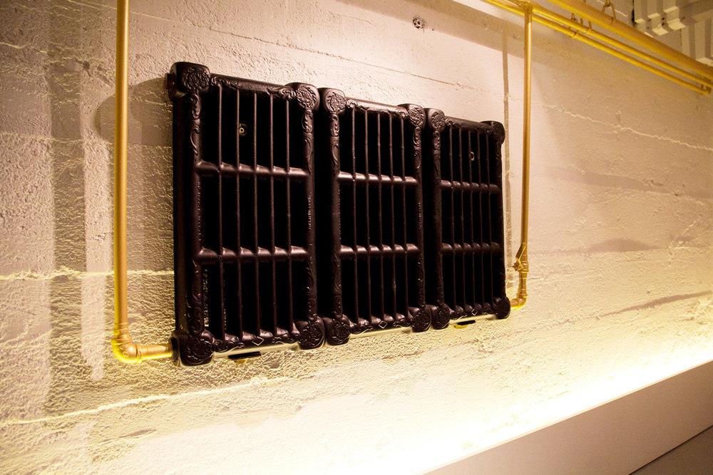 Ancien appareil de chauffage à eau chaude installé au mur d'un sous-sol. Tuyaux peint couleur or et radiateur fini noir. Mur de béton peint blanc