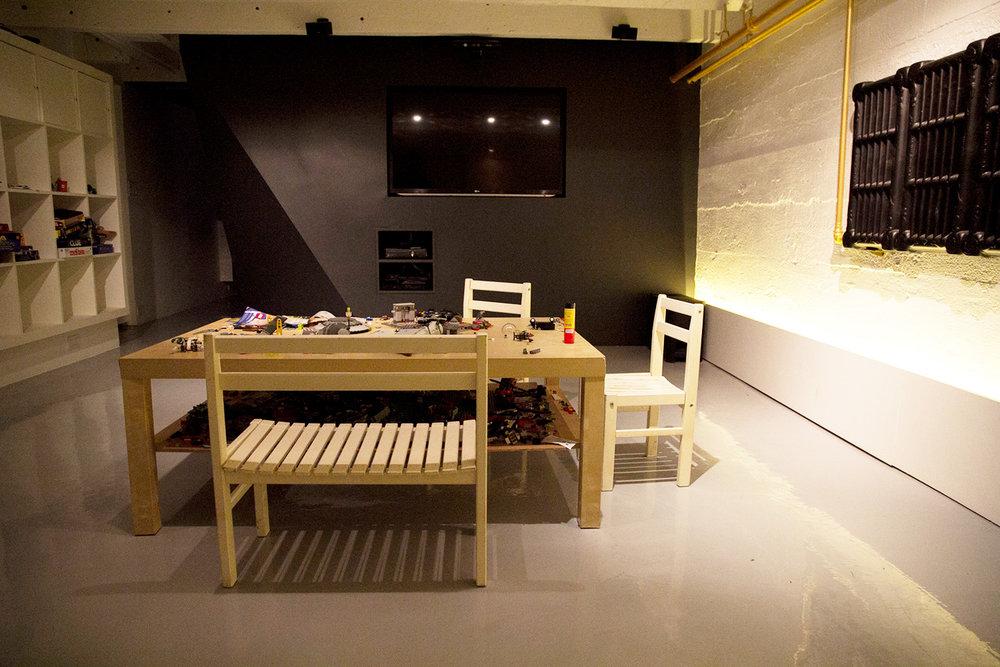 Aménagement d'un sous-sol en salle de jeux. Bibliothèque blanche. Bloc central peint noir, intégration de la télévision au mur. Mur tronquer pour faciliter la circulation.