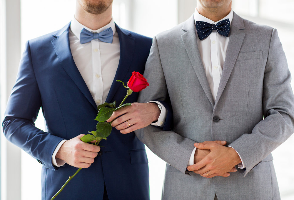 A gay couple of grooms at their wedding in tuxes holding a rose