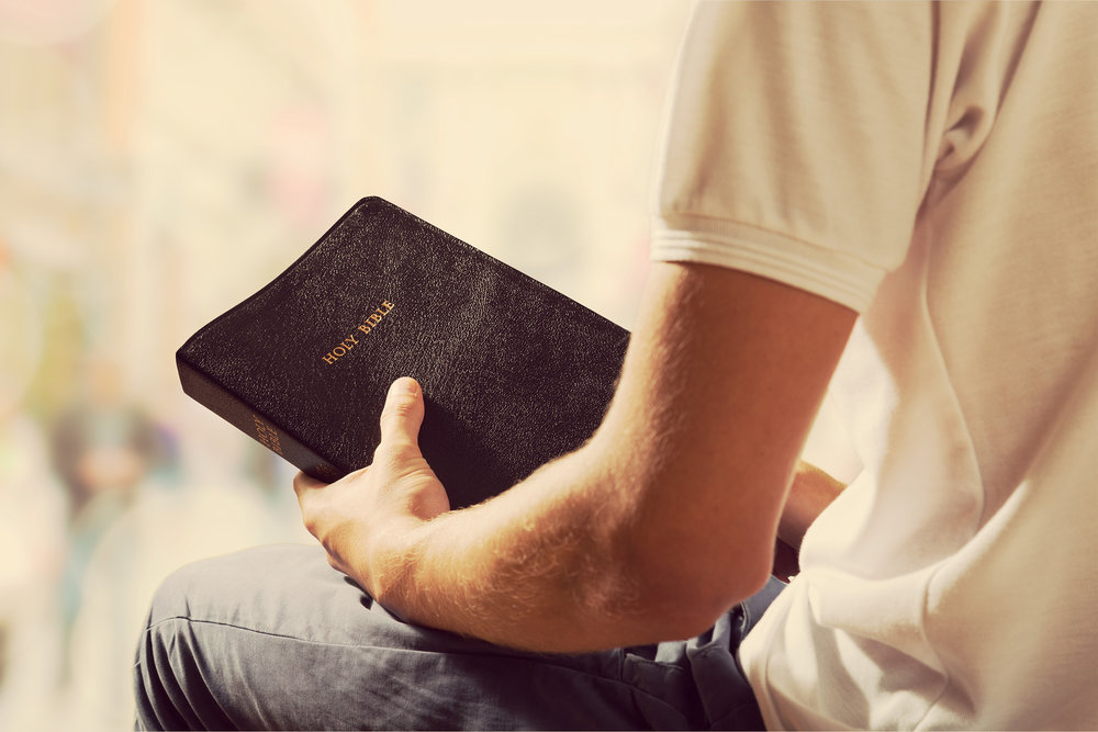 Man holding Bible to learn what Bible says about homosexuality