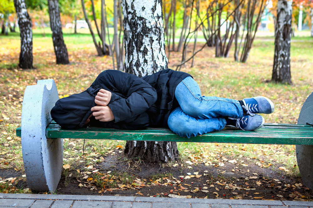 Homeless teen sleeping on park bench