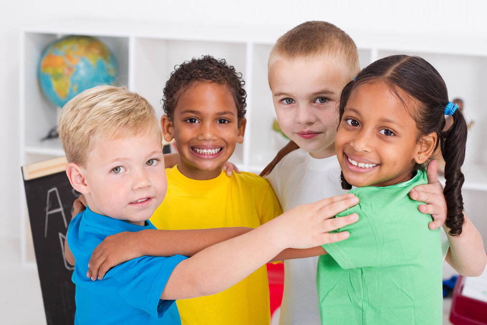 4 diverse children embracing at Sunday School for K-5 after attending part of Worship