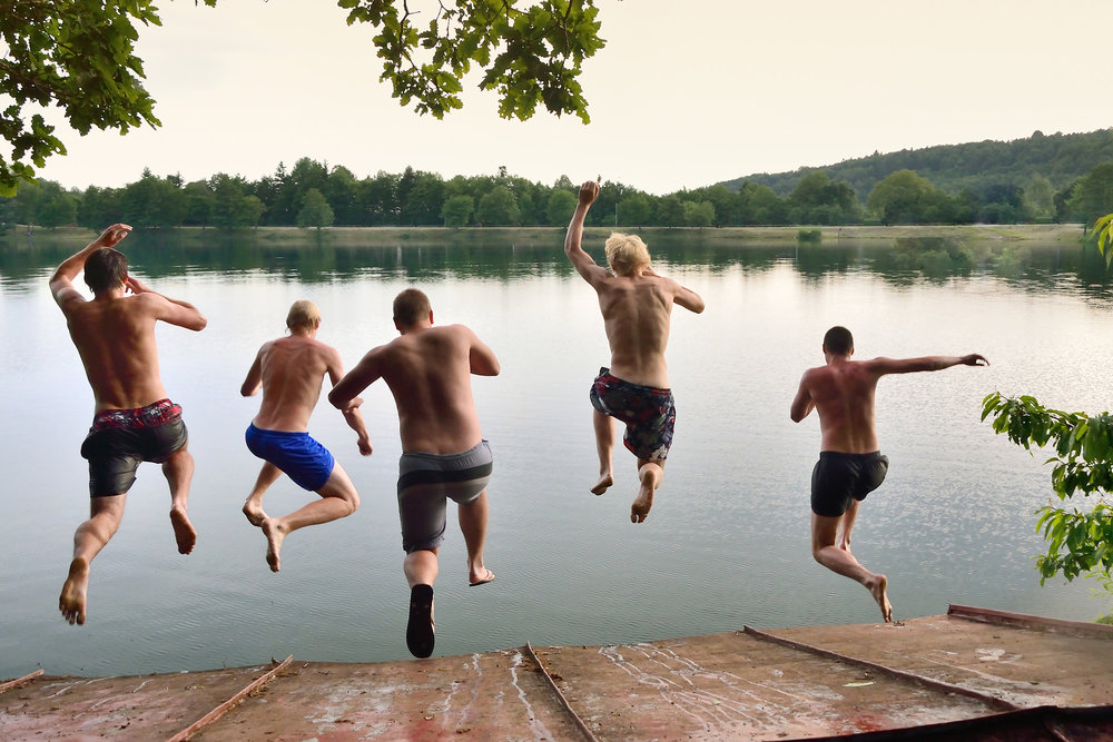 Boys jumping into lake at Church activity