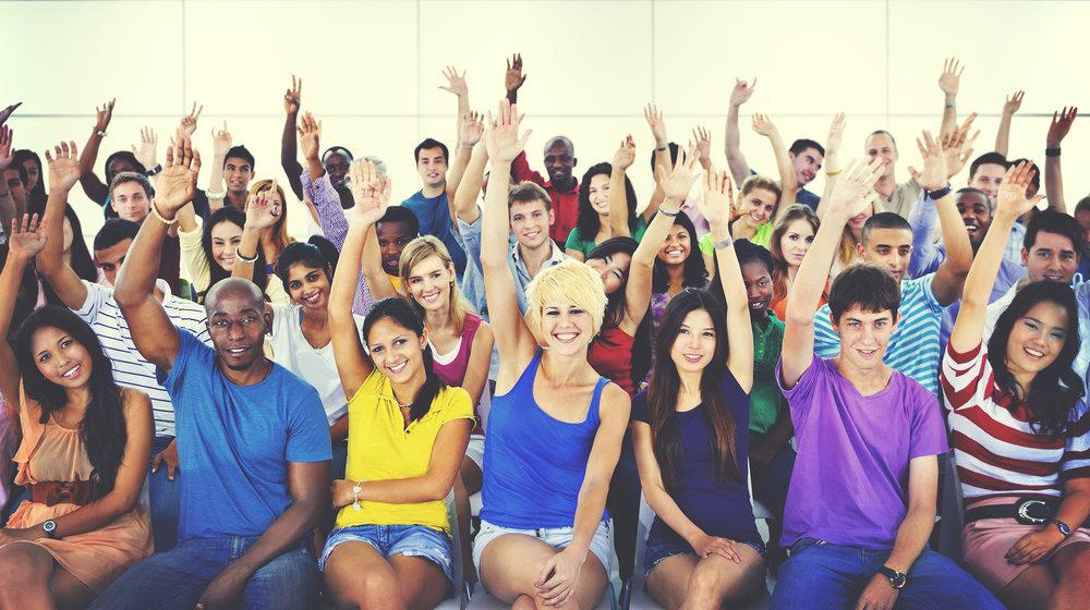 Diverse group of volunteers raising their hands. Bethel ESL teachers are volunteers