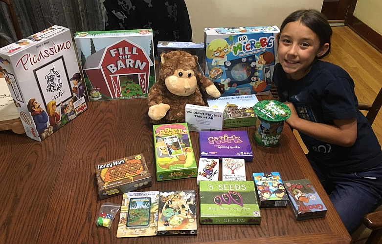 Kali received a box of games from the Indie Game Alliance and is looking forward to teaching them at SpoCon! 🎲 (Photo credit Mark Scrudder/Kallisti Scrudder)