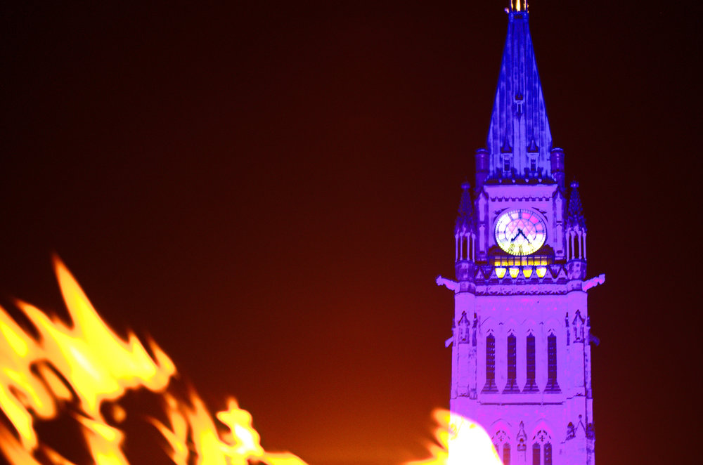 Canada's Parliaments Peace Tower lit up in a purple light on Nov 15th 2016 in response to the London Woman Abused Women's Centre #WearPurple and #ShinetheLight campaign. The flame in the foreground is from the Centennial Flame fountain.