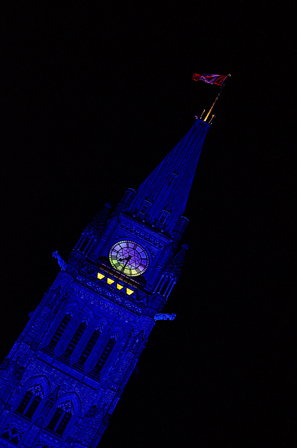 The Peace Tower glows purple in the night. The clock tower is a striking landmark of Ottawa's skyline.