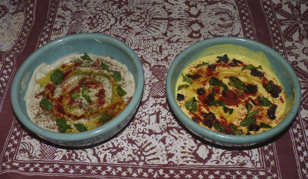Baba ganoush garnished with dill, mint and paprika; humus garnished with mint, paprika and black olives. The addition of fresh turmeric to the humus gives it a lovely golden colour.