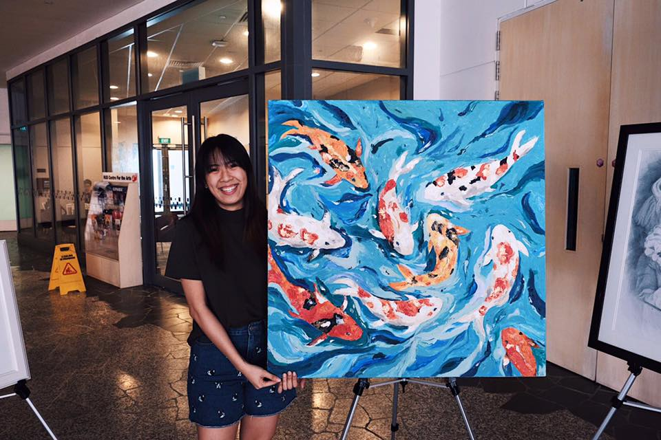 """We met with Tiara to learn more about her Koi painting that was featured at heART BUZZ 2017.   """"Actually it was quite a random painting. There was no particular reason why I chose to draw koi. I guess that's something good about art-- you can plan as you go! The painting is acrylic on canvas with impasto gel and texture paste. Since it was around Chinese New Year, I was going for more of an oriental feel.  """"The earliest painting I remember painting is of a goldfish! I never actually finished it and my mum had to help me. My mum tried to expose me to art and all sorts of things. It was a hit and miss thing, and I guess it was a miss when I was younger because I didn't really paint it in the first piece.  """"I only started taking art seriously just before Med school began! I wasn't even intending to start painting. I was actually just waiting for a friend to finish a painting and she had a spare canvas and I decided to go for it! So I guess I still feel like quite an amateur.  """"To me art is a form of self expression. Maybe I'm not great at expressing myself through words but I feel like art is a medium through which you can show a side of yourself to other people in a less invasive way. Actually, a lot of the work that I do is abstract. I do consider it to be a hobby that I hope to continue even as I get busier.  """"I'm honestly still quite an amateur and the first time I featured my artwork was in a friend's mum's Instagram post! But jokes aside, my works have also been featured at White Coat Ceremony and DnD and I've done some commissioned work outside as well :)"""""""