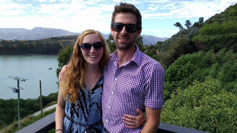 Our engagement - Smiling the day after our engagement with the view of Charteris Bay behind us.
