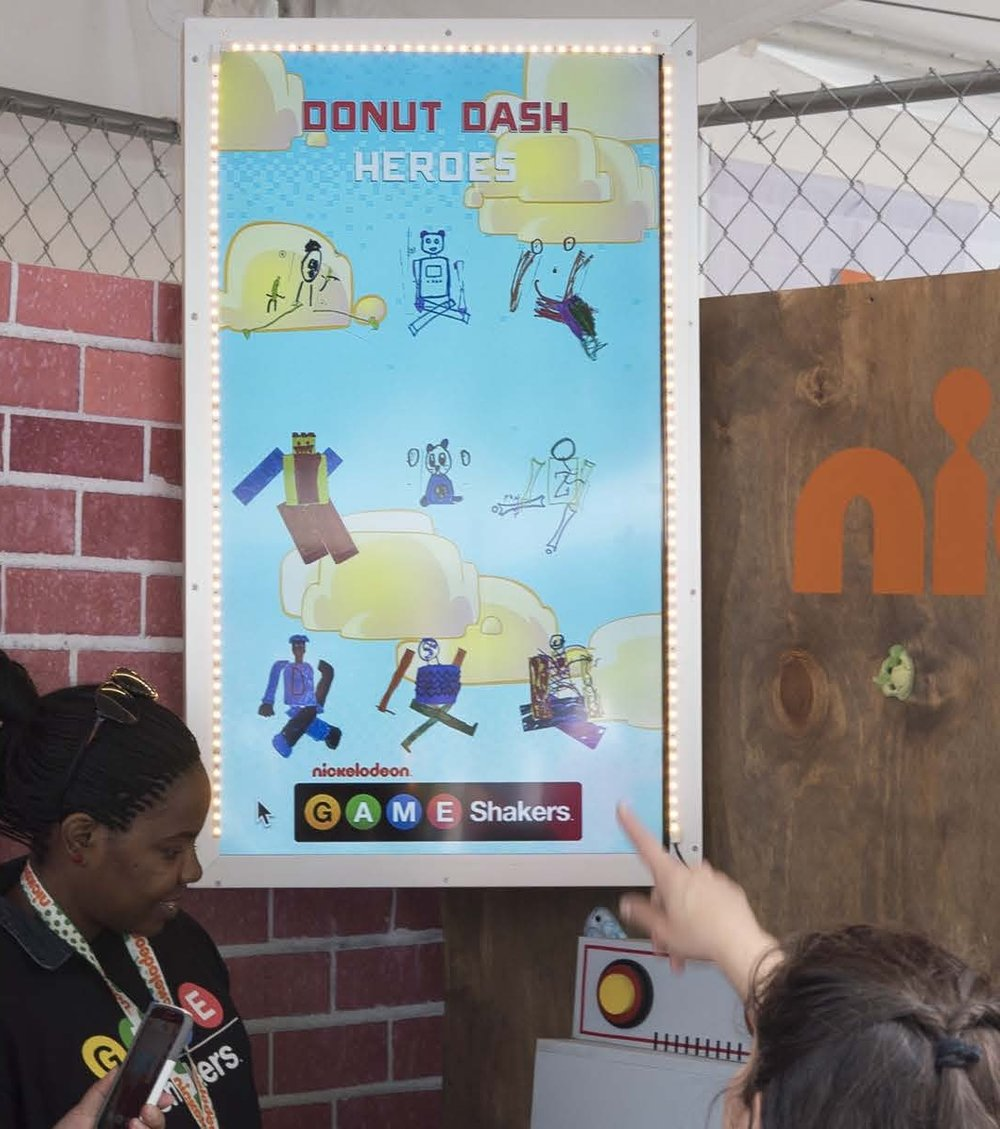 - Interacting with their own creation was powerful for the kids. After they played donut dash using the character they created, that character would appear on a large screen so all the other kids in the booth could share in the creation. The kids were then directed to a print station where a photo of their character was spit out through a slot in the brick wall and inserted into a branded Game Shakers notebook. Each child was able to take home a Game Shaker's branded notebook with their character on the cover. After Maker Faire, kids got to relive the experience once again as a link of their individual character, as well as all of the other characters created at the boot, was emailed to them.