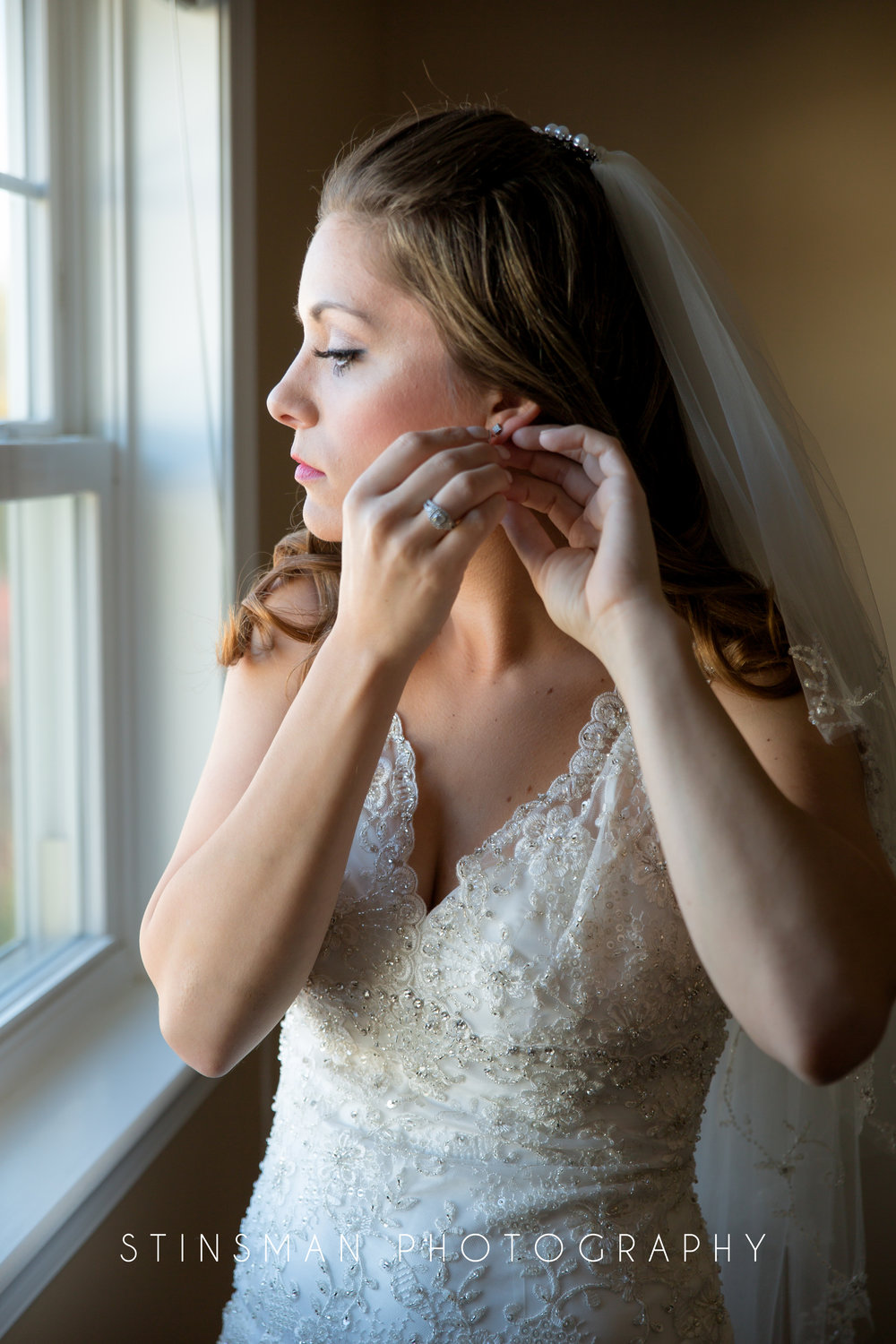 bride putting on her diamond earrings