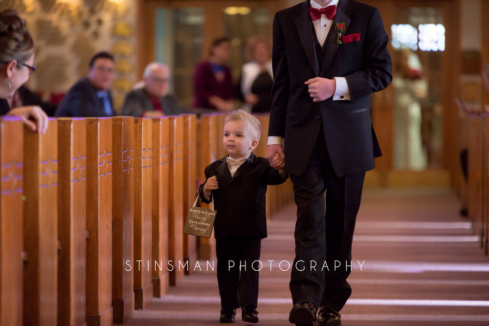 son walking down the aisle at the church