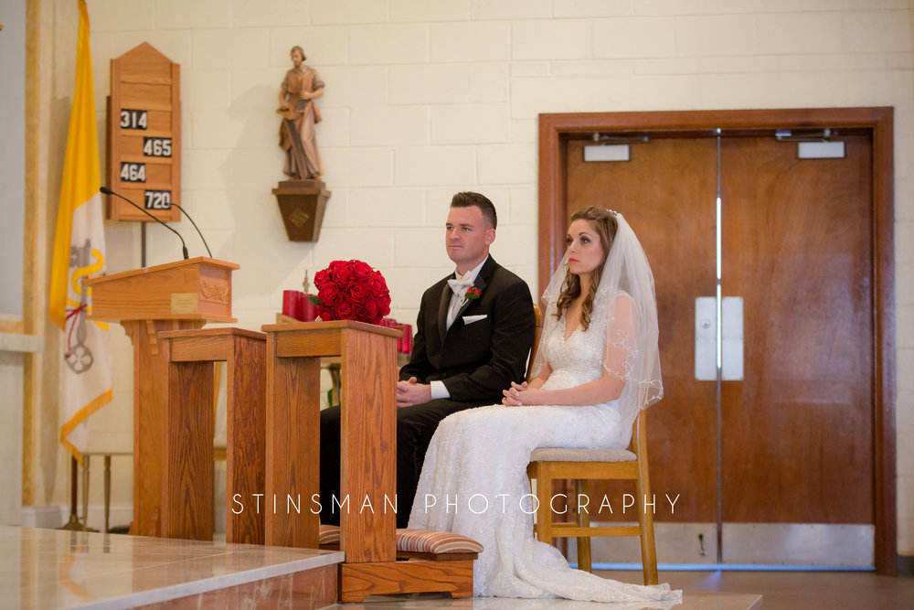 bride and groom stating their vows to each other in a catholic church