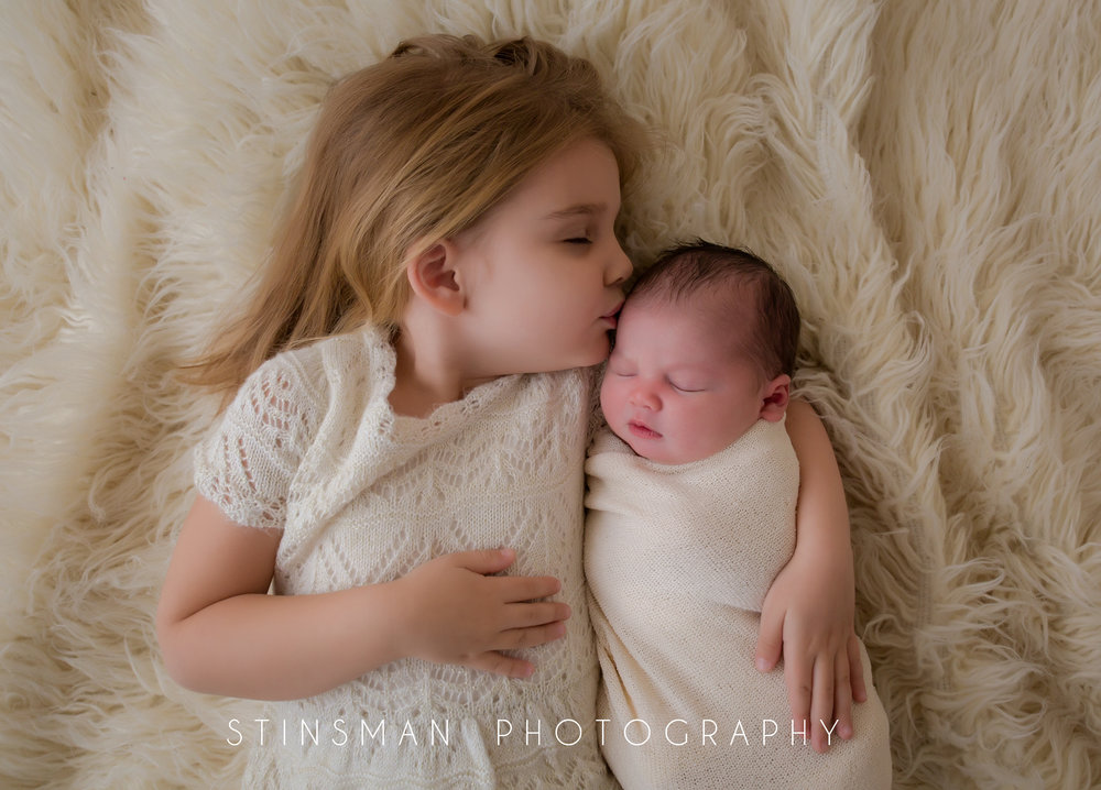 little girl kissing her baby sister while laying on a white rug