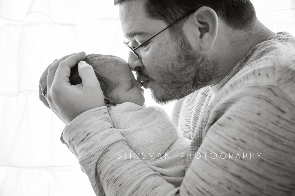 new dad kissing his little girl in black and white