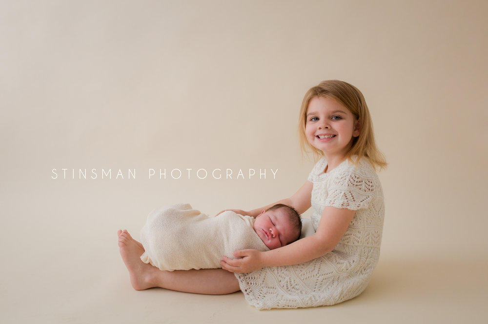 big sister holding her little sister in a cream wrap on her legs