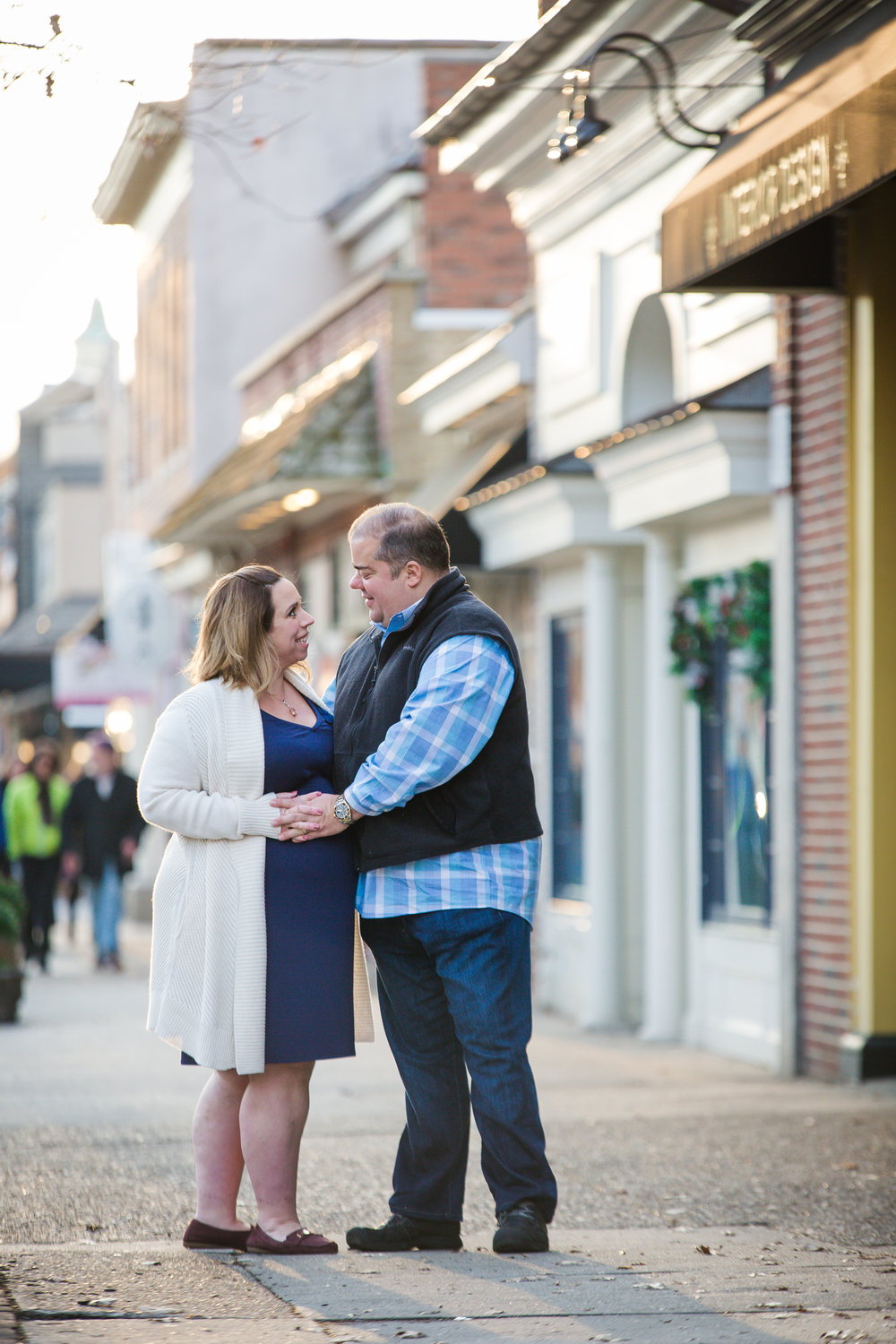 couple holding hands on a pregnant belly in haddonfield nj