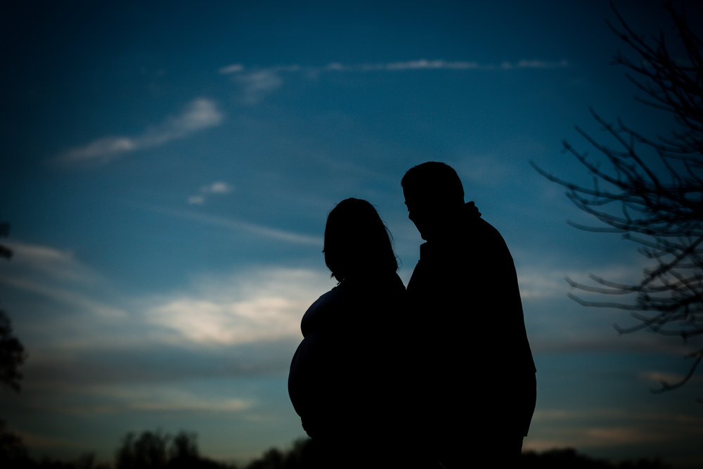 silhouette photo of a pregnant mom and dad