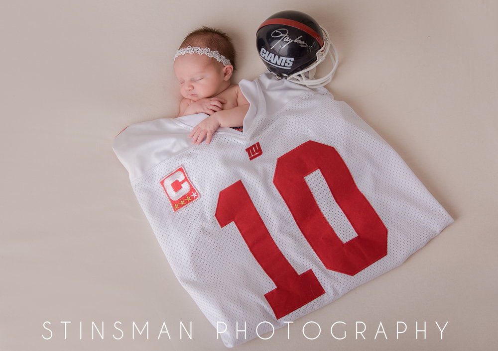Newborn girl under a giants football jersey and helmet