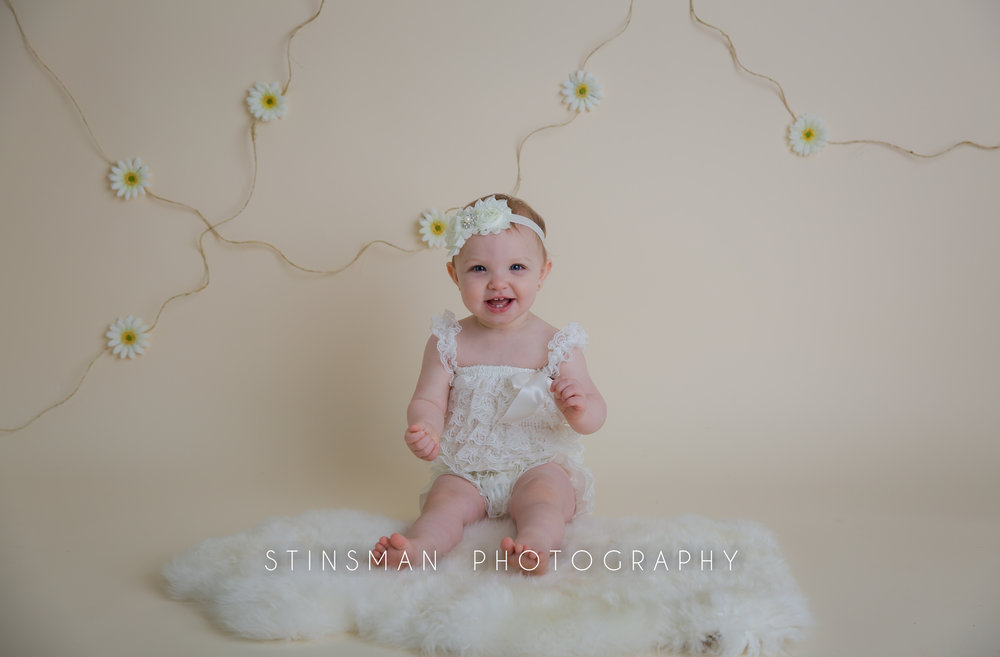 little girl photos for her first birthday wearing a white outfit and smiling