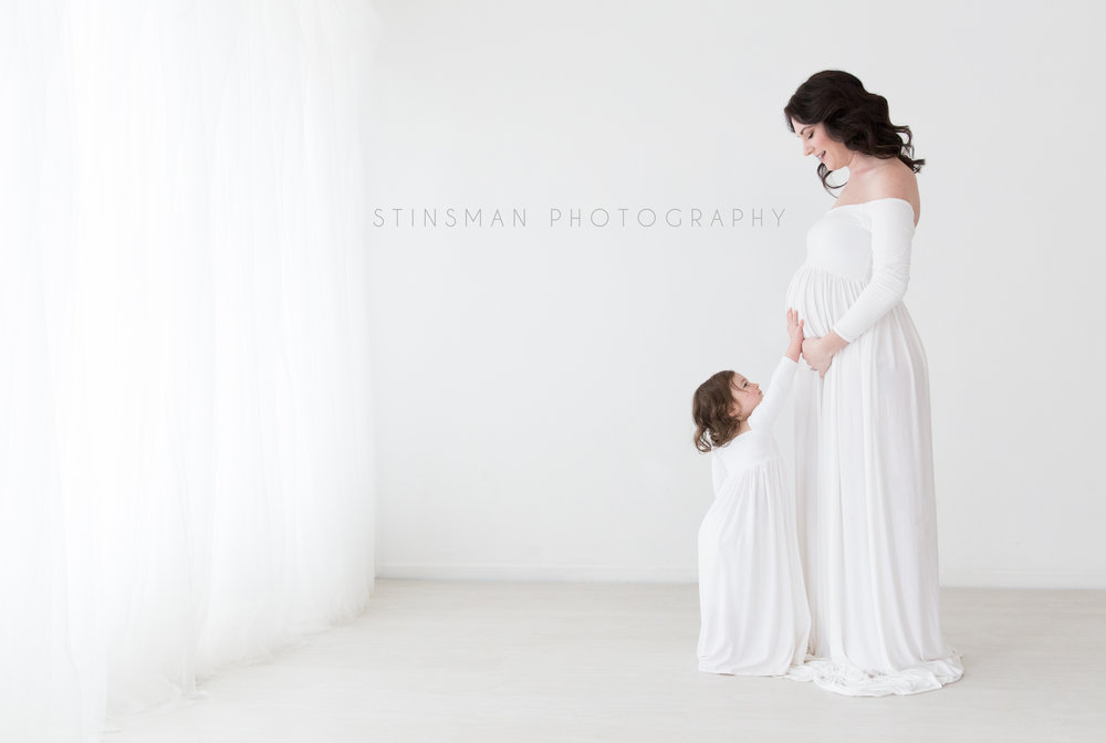 Mom and daughter wearing white gowns holding moms belly in Burlington nj photo studio