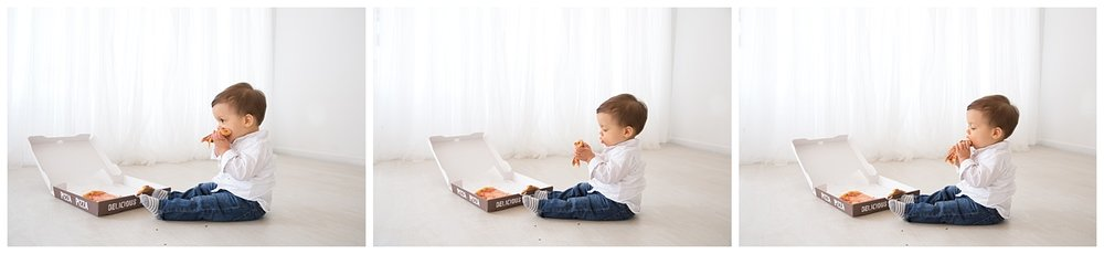 little boy eating pizza in front of the window in burlington new jersey studio