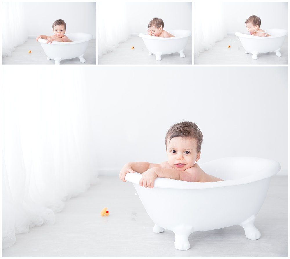 little boy posing in the tub with his rubber duckies for his first birthday photo shoot in burlington new jersey