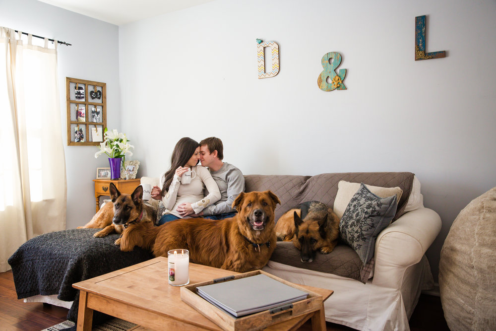 Mom and dad snuggling on the couch in their Cinnaminson nj home with three rescue dogs for maternity photo shoot