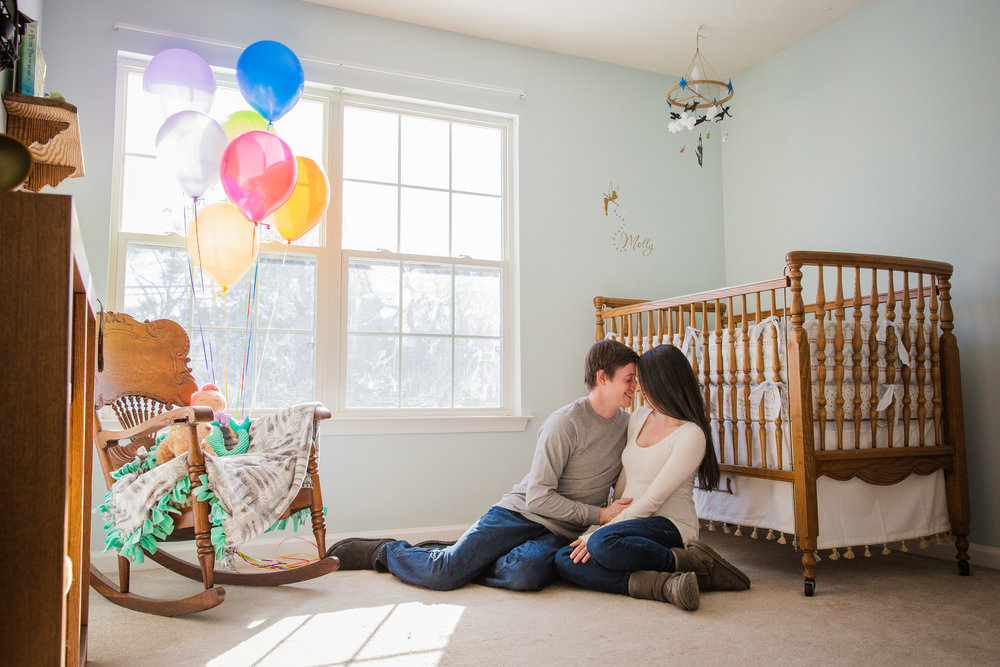 Mom and dad snuggling in their home in their new baby's nursery with rainbow balloons in Cinnaminson nj photo shoot
