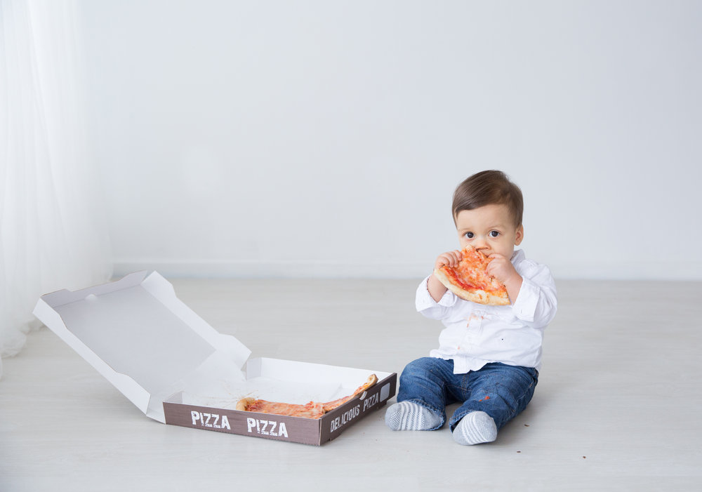 one year old baby eating pizza for his first birthday photo shoot in burlington new jersey