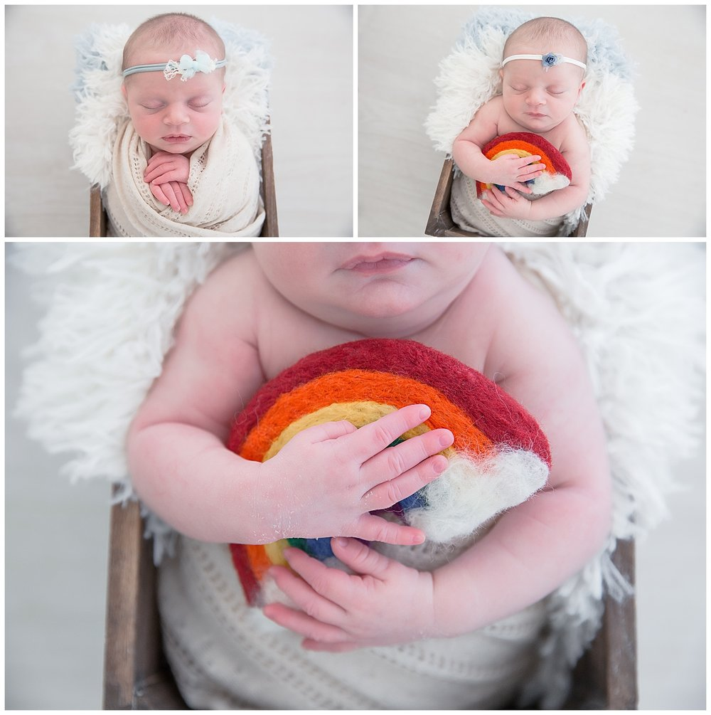 newborn baby girl holding a rainbow in burlington new jersey photo shoot