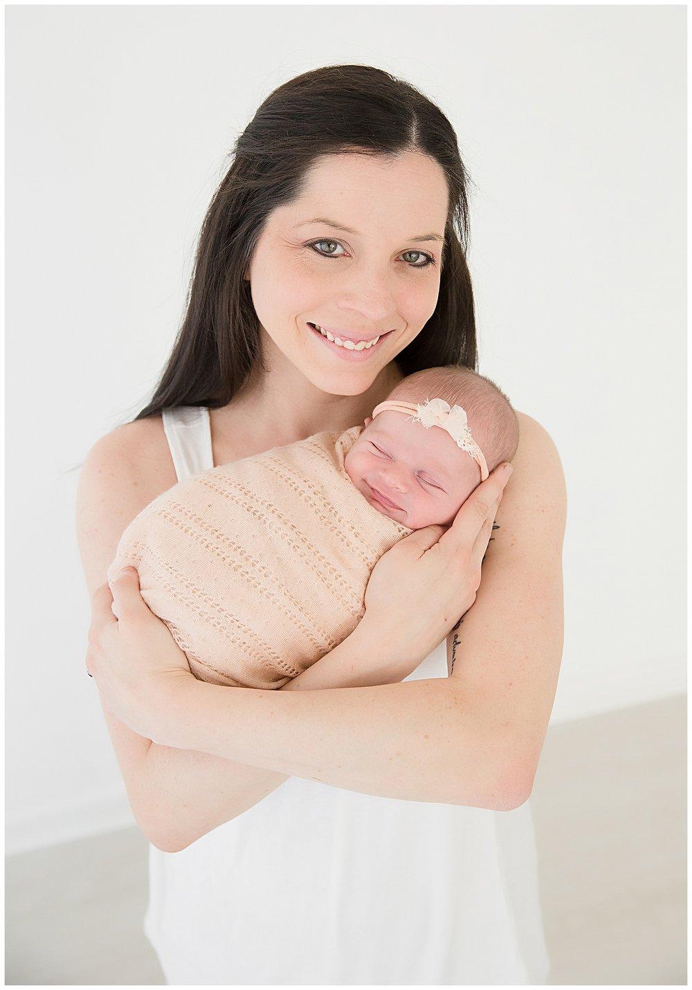 mom holding her baby girl smiling